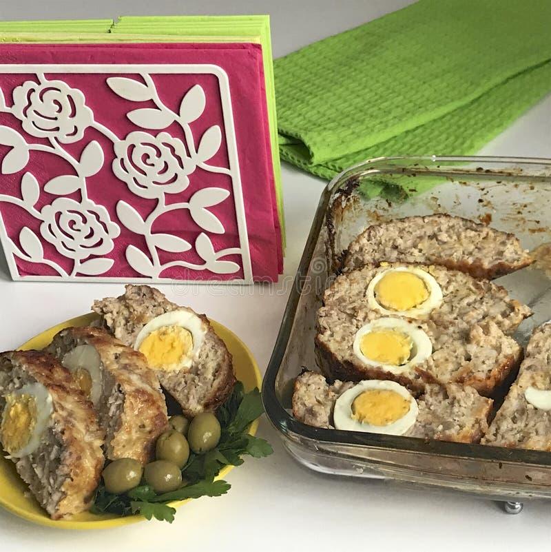 Preparazione dei polpettoni tritati Come uovo sodo di riempimento Le fette del rotolo finito sono su un piatto con le olive ed i  fotografia stock