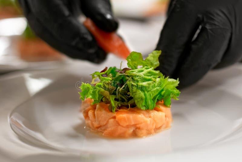 Preparazione del dispositivo d'avviamento di color salmone marinato con insalata fotografia stock