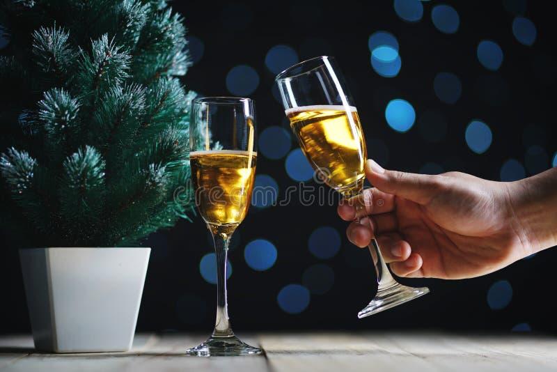 Preparazione della luce scura di incandescenza di Champagne Besides Small Christmas Tree fotografie stock libere da diritti