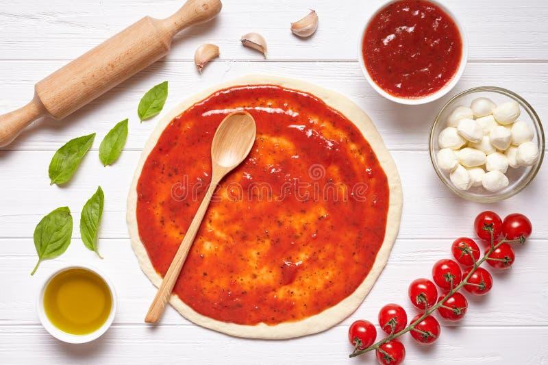 Preparazione della pizza Ingredienti di cottura sul tavolo da cucina: pasta rotolata con la salsa di pomodori immagine stock