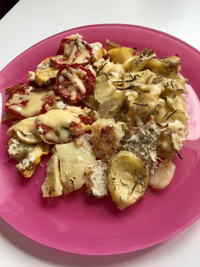 Preparazione delle patate, dello zucchini e dei pomodori nel forno Le verdure sono presentate su un piatto, spruzzato con formagg immagine stock