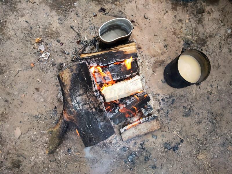 Preparazione di alimento su fuoco Giocatore di bocce turistico su fuoco, cucinante nell'aumento fotografia stock