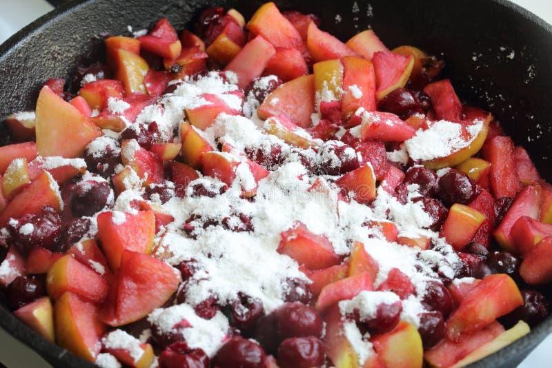 Preparazione di un riempimento per la mela - crostata di ciliege (strudel) immagini stock