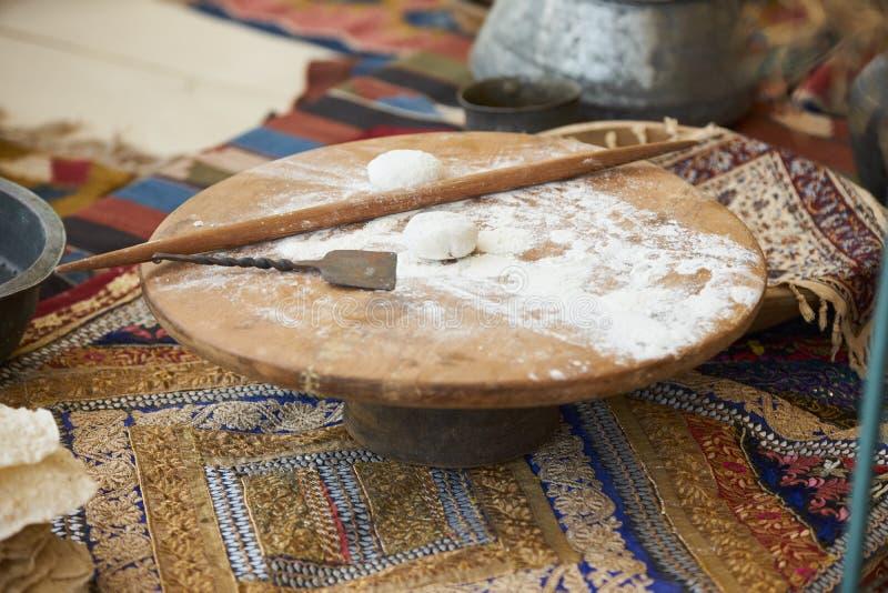 Preparazione turca tradizionale del pane della pita di cucina Pasta su un bordo di legno rotondo immagine stock