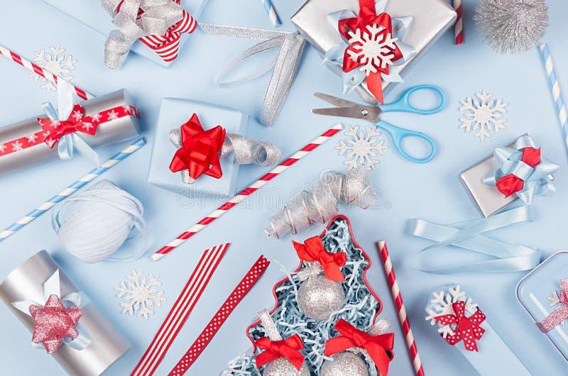 Preparazioni di Natale - contenitori di regalo differenti festivi nel colore rosso, blu e metallico con i nastri di seta, albero  fotografia stock