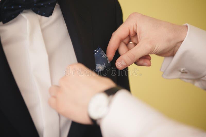 Preparazioni per le nozze Groomsmen che aiutano sposo che si prepara di mattina nella stanza fotografie stock