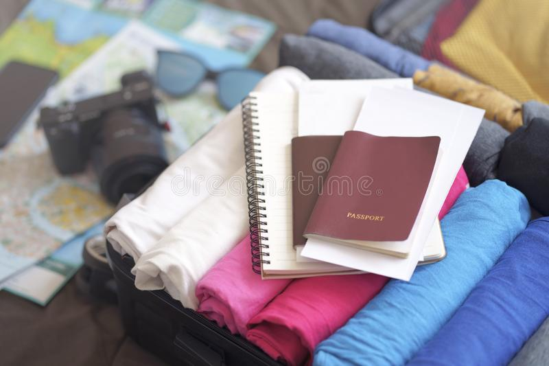 Prepare accessories for new journey, packing clothes in suitcase bag on bed stock photo