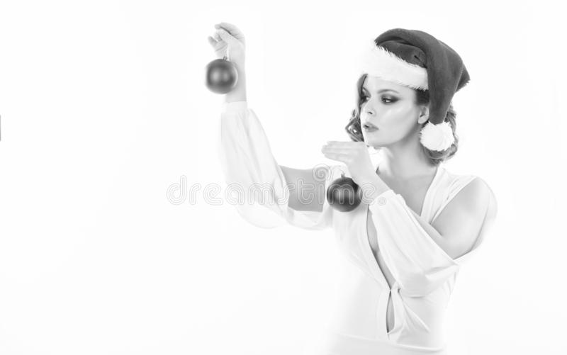 Prepare for christmas. Woman wear sexy dress and santa hat hold decorative balls on white background. Girl with makeup stock images