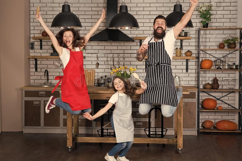 Prepare delicious meal. Breakfast time. Family having fun cooking together. Teach kid cooking food. Cooking together. Family mom dad and daughter wear aprons royalty free stock image