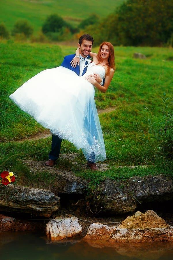Prepare detener a su novia en sus brazos en paisaje hermoso fotos de archivo