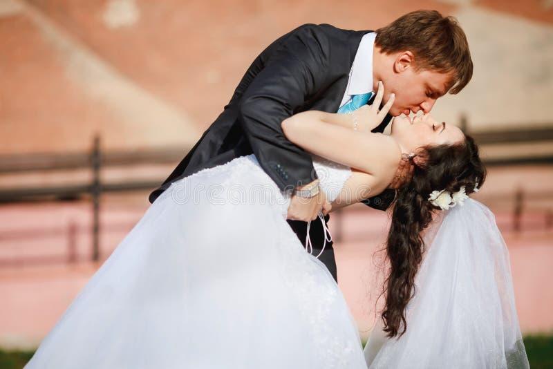 Prepare a la novia inclinada apacible, deteniéndola en sus brazos fotos de archivo