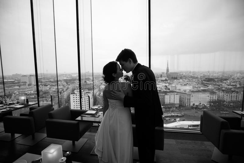Prepare la oferta trasera del ` s de la novia de los controles que la besa en un restaura vacío fotografía de archivo