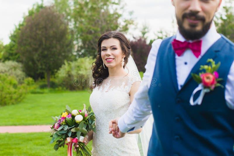 Prepare llevar a cabo la mano de su novia feliz sonriente fotos de archivo