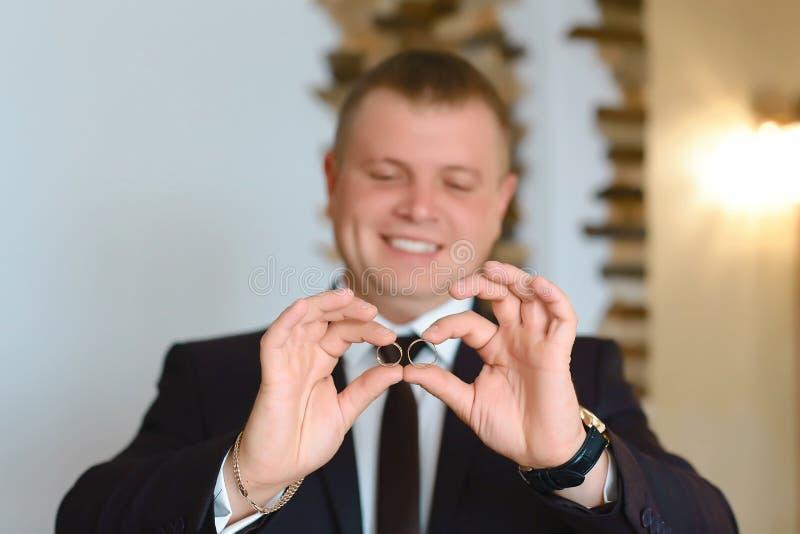 Prepare llevar a cabo los anillos de bodas en la palma en el traje, la mano del novio, anillo de bodas en mano del novio imagen de archivo libre de regalías