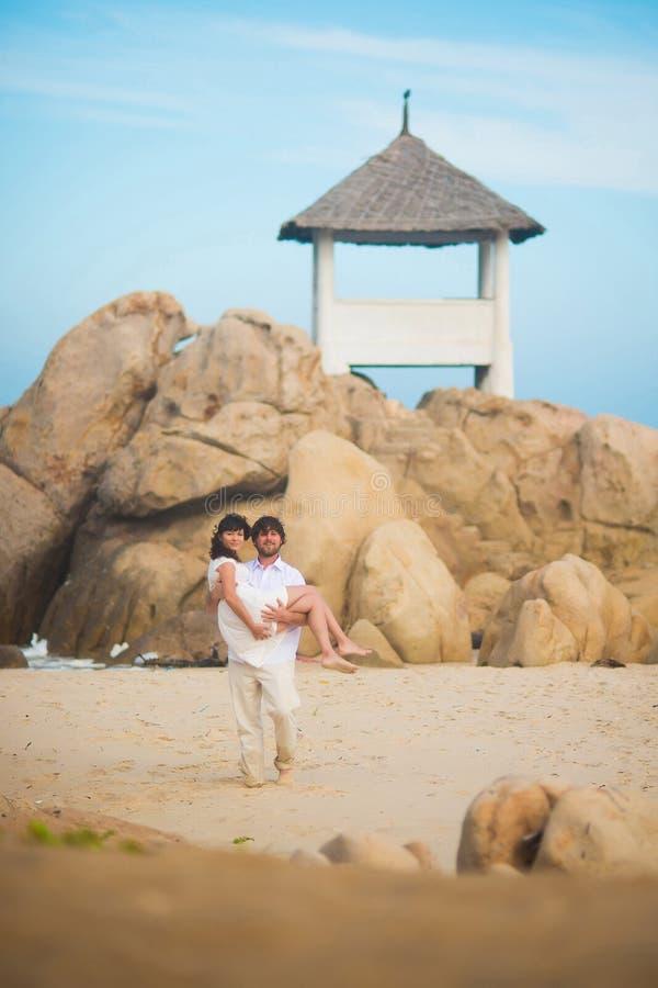 Prepare los controles la novia en sus brazos contra un terreno rocoso imagen de archivo