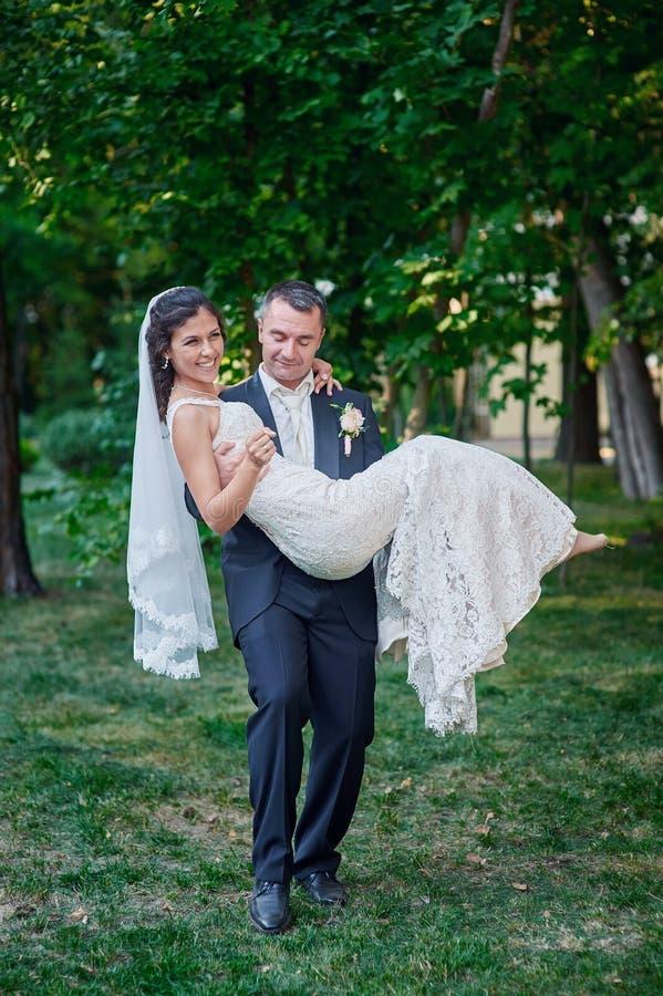 Prepare los controles su novia en sus brazos y sonrisas de la felicidad imagenes de archivo