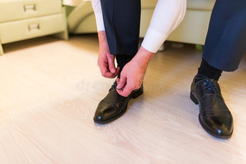Prepare los zapatos que llevan el día de boda, atando los cordones y la preparación Hombre de negocios que se viste para arriba c foto de archivo