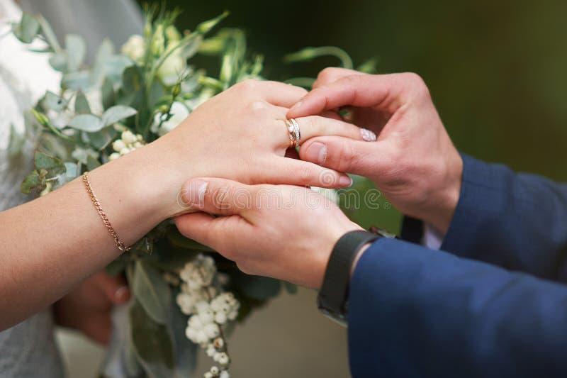 Prepare a mão que põe uma aliança de casamento sobre o dedo da noiva fotografia de stock royalty free