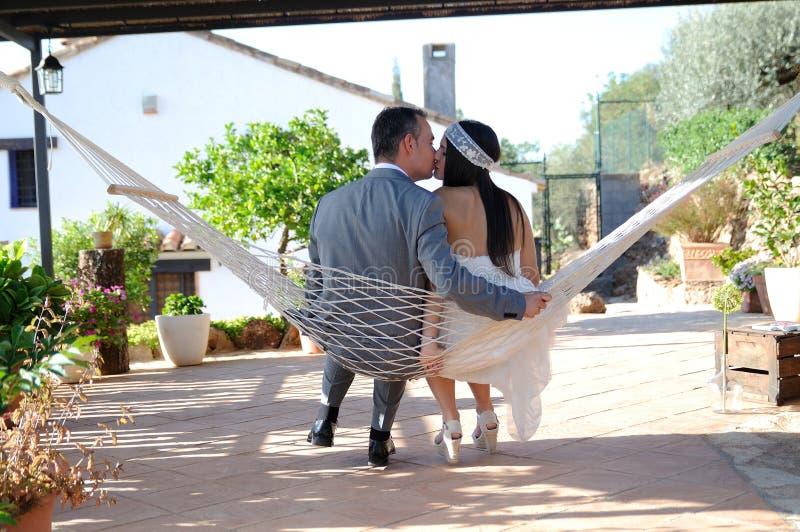Prepare o assento de beijo da noiva em uma corda da rede foto de stock