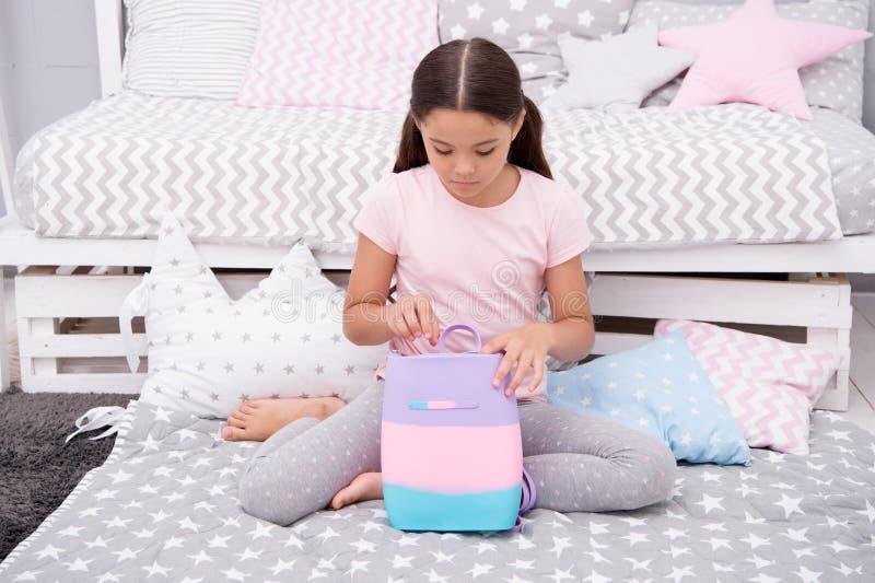 Prepare o saco para amanhã A criança da menina senta-se na cama com saco ou os cosméticos ensacam em seu quarto A criança prepara imagem de stock royalty free