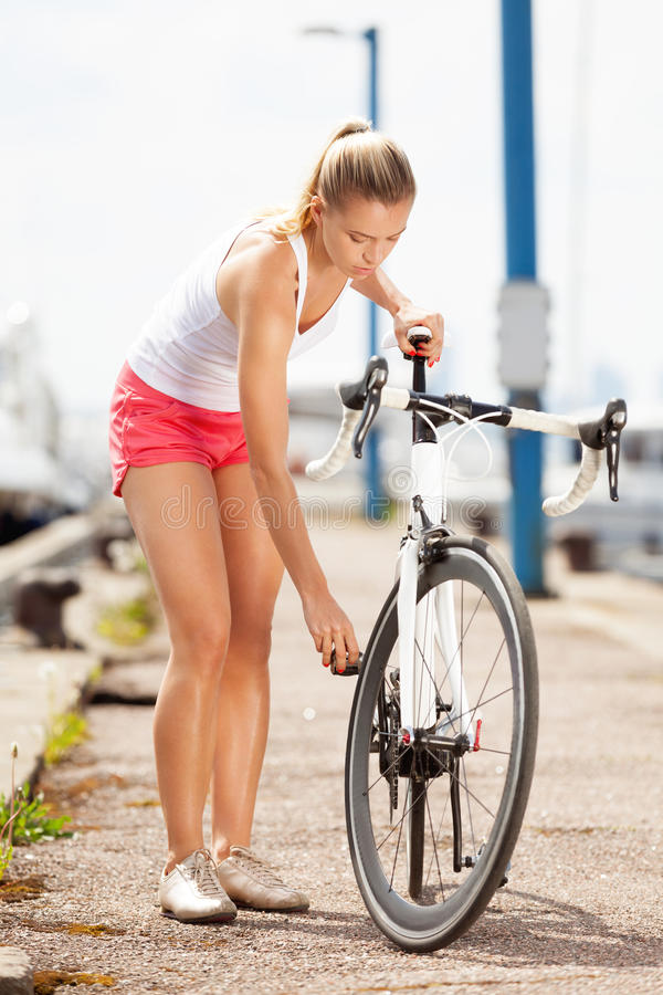 Prepare for a ride. Woman preparing for a bicycle ride stock images