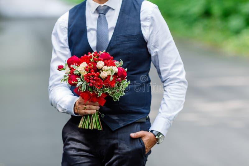 Prepare sostenerse en manos ramo nupcial delicado, costoso, de moda de la boda de flores en marsala y colorsry rojo atadas al b fotos de archivo