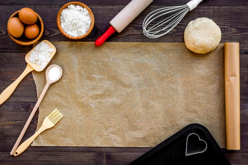 Prepare to baking. Dough ball near cookware on dark wooden background top view. Mock up with baking paper royalty free stock photo