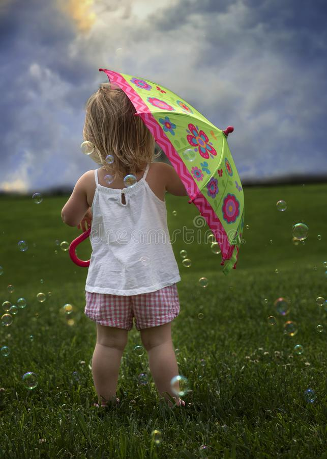 Bubbles and storms rolling in!. Prepare the umbrellas! Bubbles and Storms are rolling in. Cute little toddler preparing for storm royalty free stock photo