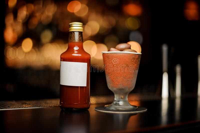 Prepared Bloody Mary cocktail in the bottle and glass decorated with red powder with little plate of olives on it royalty free stock images