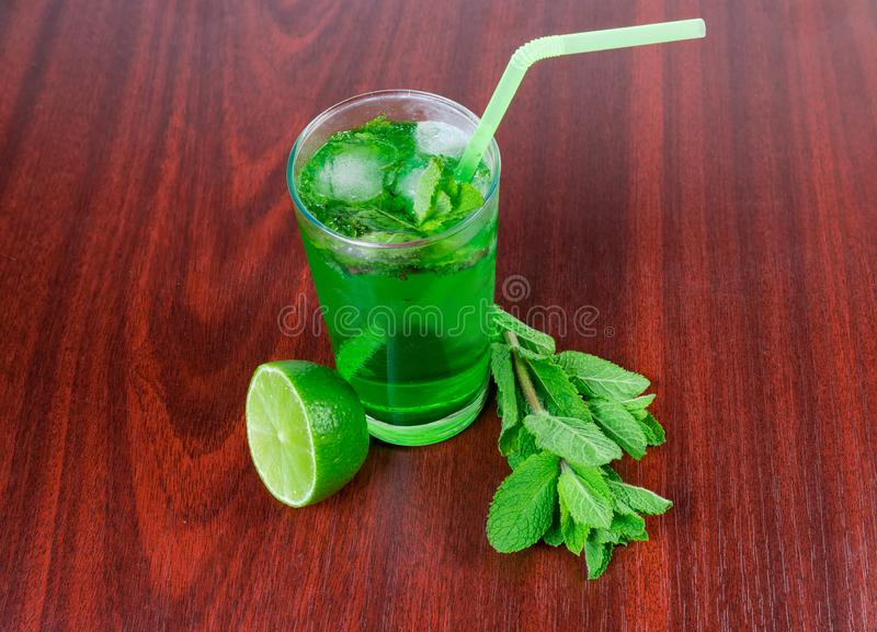 Cold mint drink, mint twigs and lime on wooden table. Prepared cold drink with freshly squeezed lime and mint in glass with drinking straw, mint twigs and half stock images