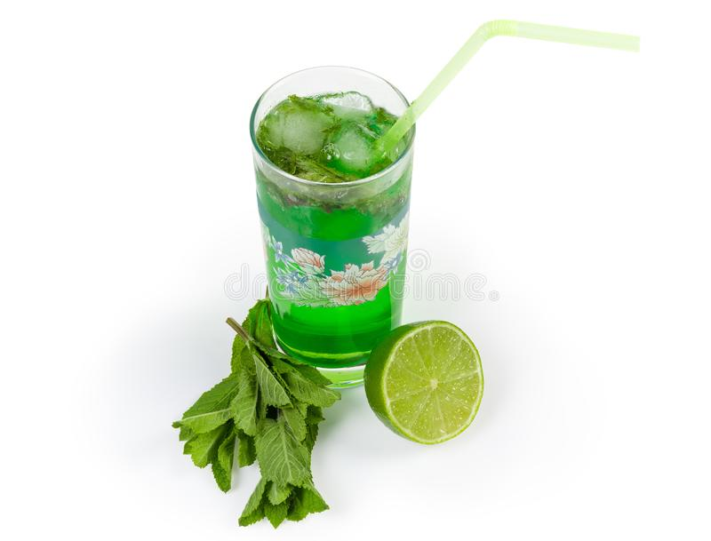 Cold mint drink, mint twigs and lime on white background. Prepared cold drink with freshly squeezed lime and mint in glass with drinking straw, mint twigs and royalty free stock images
