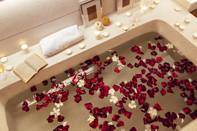 Spa bath with petals and candles. Prepared luxury spa bath decorated with flower petals and candles, top view from above royalty free stock images