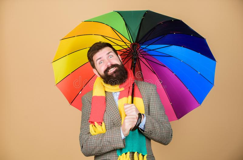 Prepared for rainy day. Carefree and positive. Enjoy rainy day. Predict future weather trends. Man bearded guy hold. Colorful umbrella. It seems to be raining royalty free stock photography