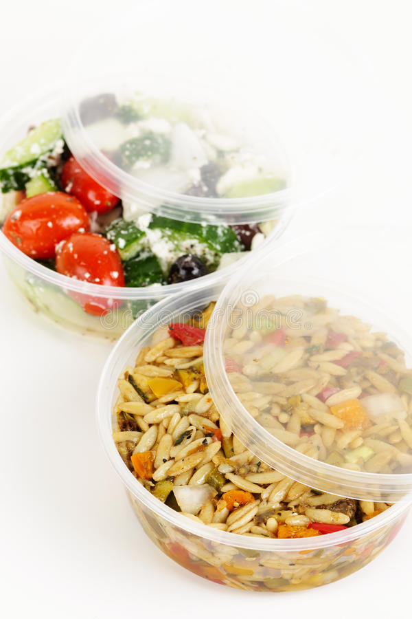 Prepared salads in takeout containers. Two servings of prepared salad in plastic takeaway containers stock images