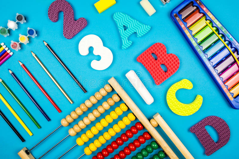 Prepared for the school. Multiple preschool and school tools laying on turquoise background royalty free stock photo