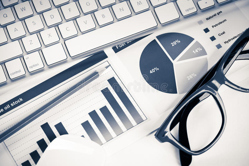 Preparing average sales report. Business workplace with keyboard glasses and financial documents on table stock photo