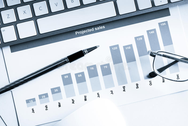 Preparing average sales report. Business workplace with keyboard mouse and papers with graphs and diagrams royalty free stock image