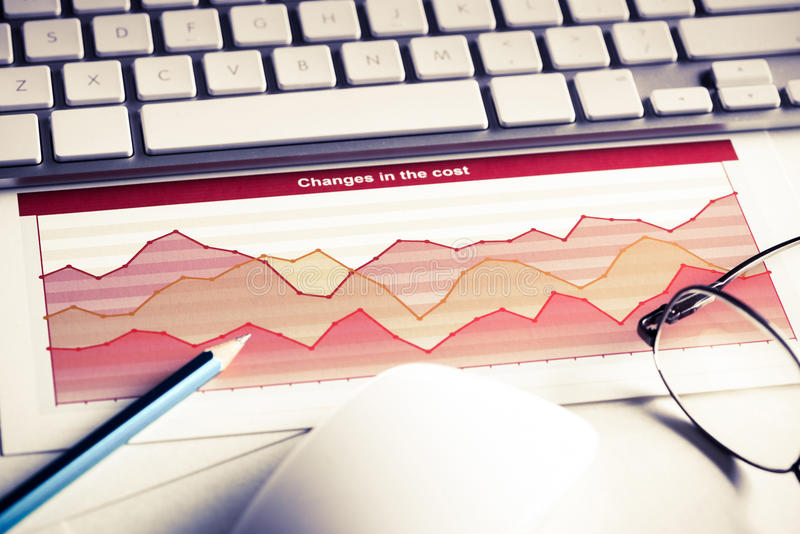Preparing average sales report. Business workplace with keyboard mouse and papers with graphs and diagrams royalty free stock images