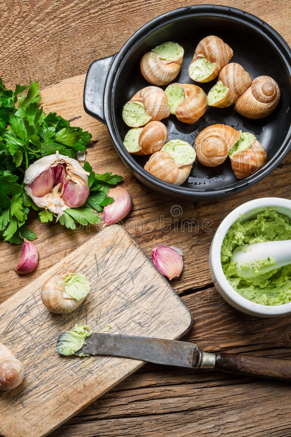 Preparing baked snails with garlic and parsley stock photos
