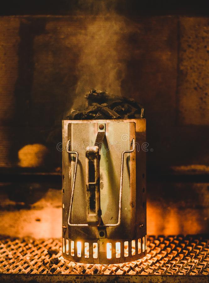 Preparing barbecue coals or briquettes in chimney starter at night. stock images