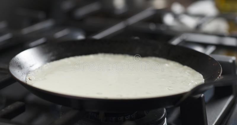 Preparing blini or crepes batter pouring on hot pan. 4k photo royalty free stock images