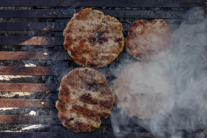 Preparing burger patties on a grill outdoors royalty free stock photo