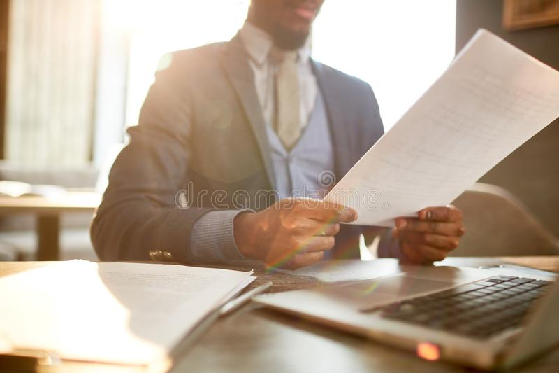 Preparing for business appointment. Young agent or financier reading papers while preparing for negotiation with one of clients royalty free stock images
