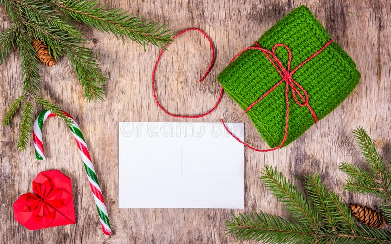 Preparing for Christmas. Blank postcard, ginger biscuit and knitted gift on old wooden board. Copy space stock photography