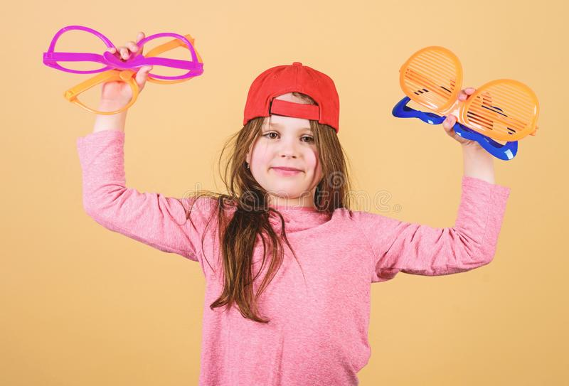 Preparing a cool party. Fashionable party girl. Adorable party girl holding fancy glasses. Cute small child choosing. Party goggles to wear royalty free stock photography