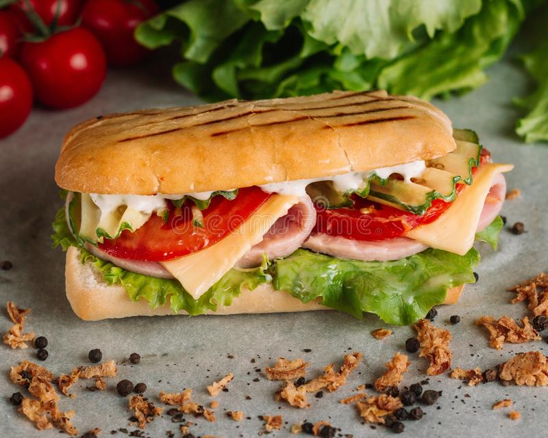 Preparing a crusty fresh ciabatta baguette sandwich in the kitchen with fresh salad ham serrano cherry tomatoes, olive stock photos
