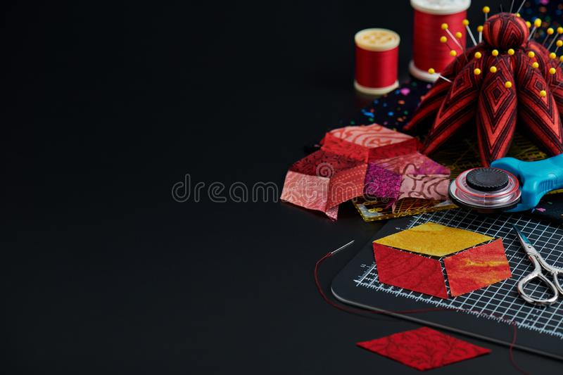 Preparing of diamond pieces of fabrics for sewing quilt, traditional patchwork, sewing and quilting accessories royalty free stock photo