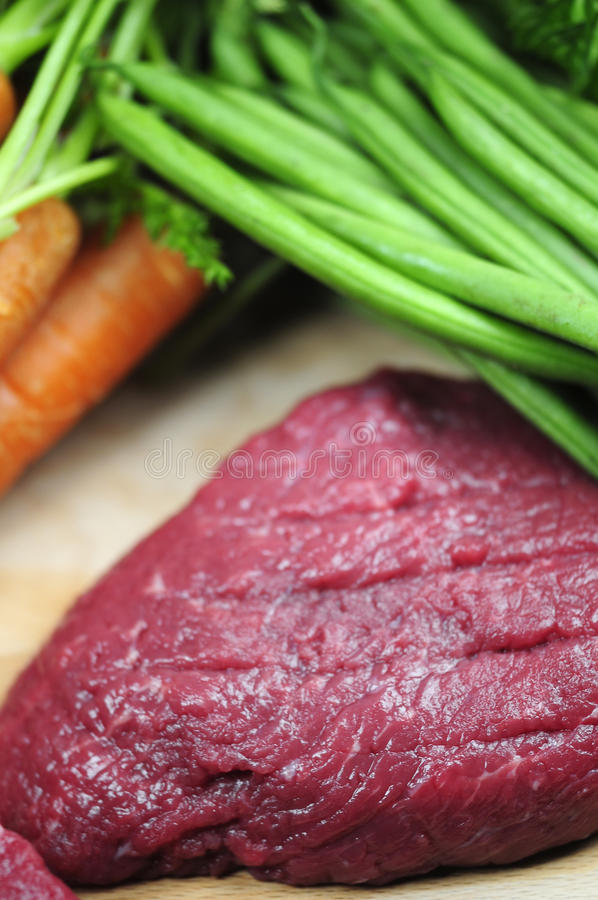 Preparing dinner. A raw steak and some uncooked vegetables stock photography