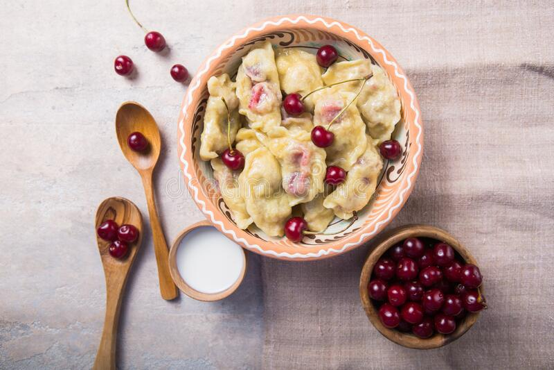 Preparing dumplings with cherry. making pierogi or pyrohy, varenyky. Traditional Russian cuisine, or  Ukrainian hand-made vareniki royalty free stock photo