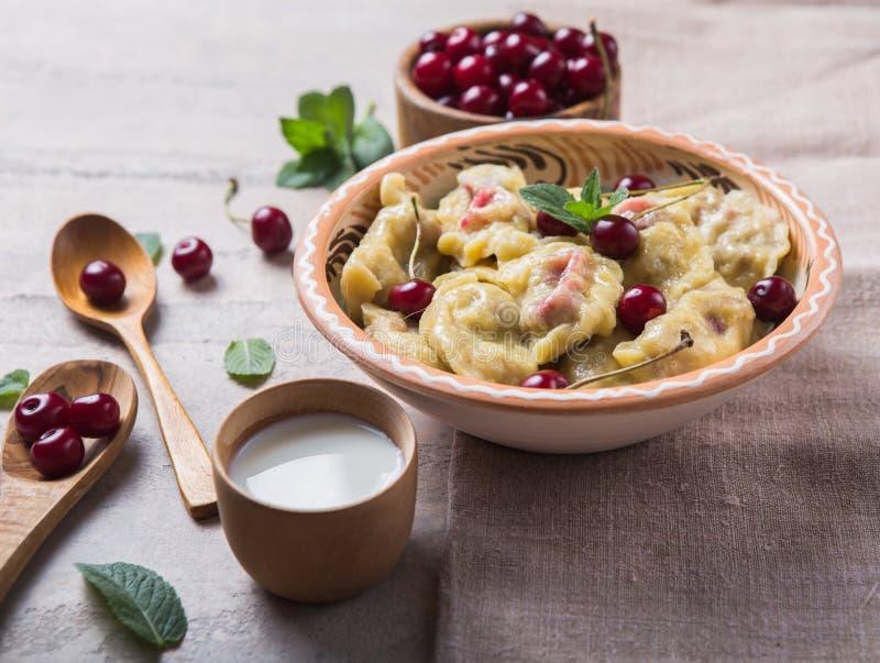 Preparing dumplings with cherry. making pierogi or pyrohy, varenyky. Traditional Russian cuisine, or  Ukrainian hand-made vareniki royalty free stock photos